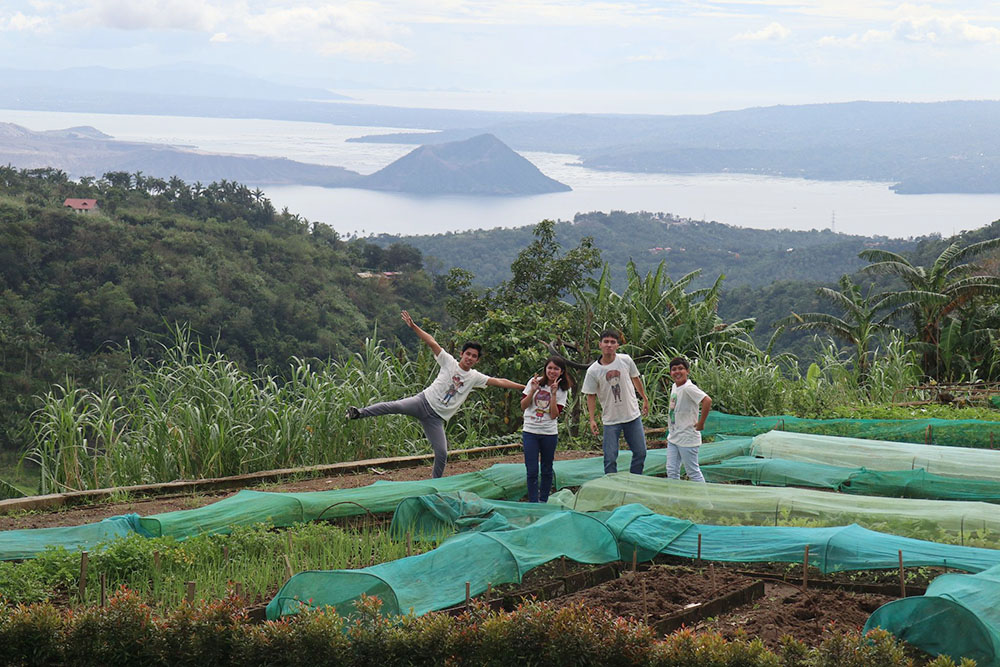 The youth in Focolare organic garden with the backdrop of Taal Volcano